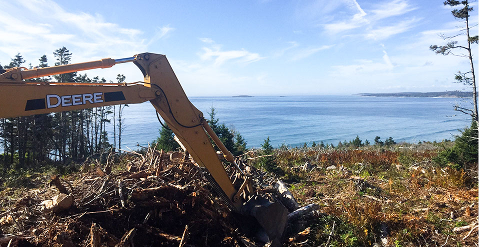 """This photo was taken by me in Clam Harbour, Nova Scotia. We were using our John Deere 120 to clear some brush and such for a new home. Picture is of the Atlantic Ocean. We are a small business of three people and have two John Deere excavators. We started the company 18 months ago and haven't looked back."""