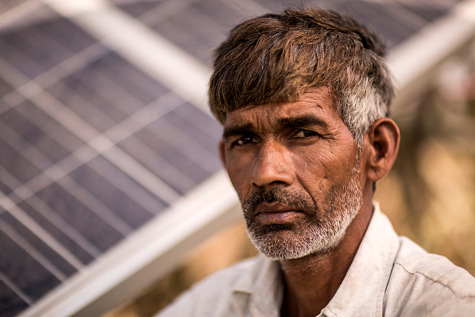 Madholal Aheer, in front of his solar panels, which he uses to power his irrigation system. Madholal, like many JIVA farmers, uses pumps to draw water from hand-cut wells that are over 60 feet deep.