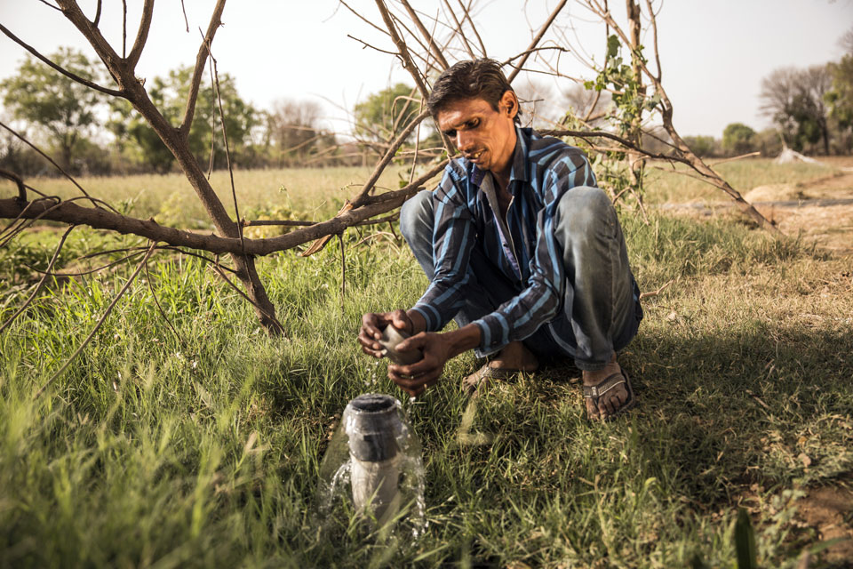 Sita's husband, Bherulal, checks the cap on an irrigation pipe that runs alongside their fields. Thanks to their increased income from JIVA-taught practices, Bherulal and Sita continue to invest in their farm. In 2015, they invested 40,000 rupees to deepen their well. They also recently invested 25,000 rupees to level their farmland making it easier to irrigate.