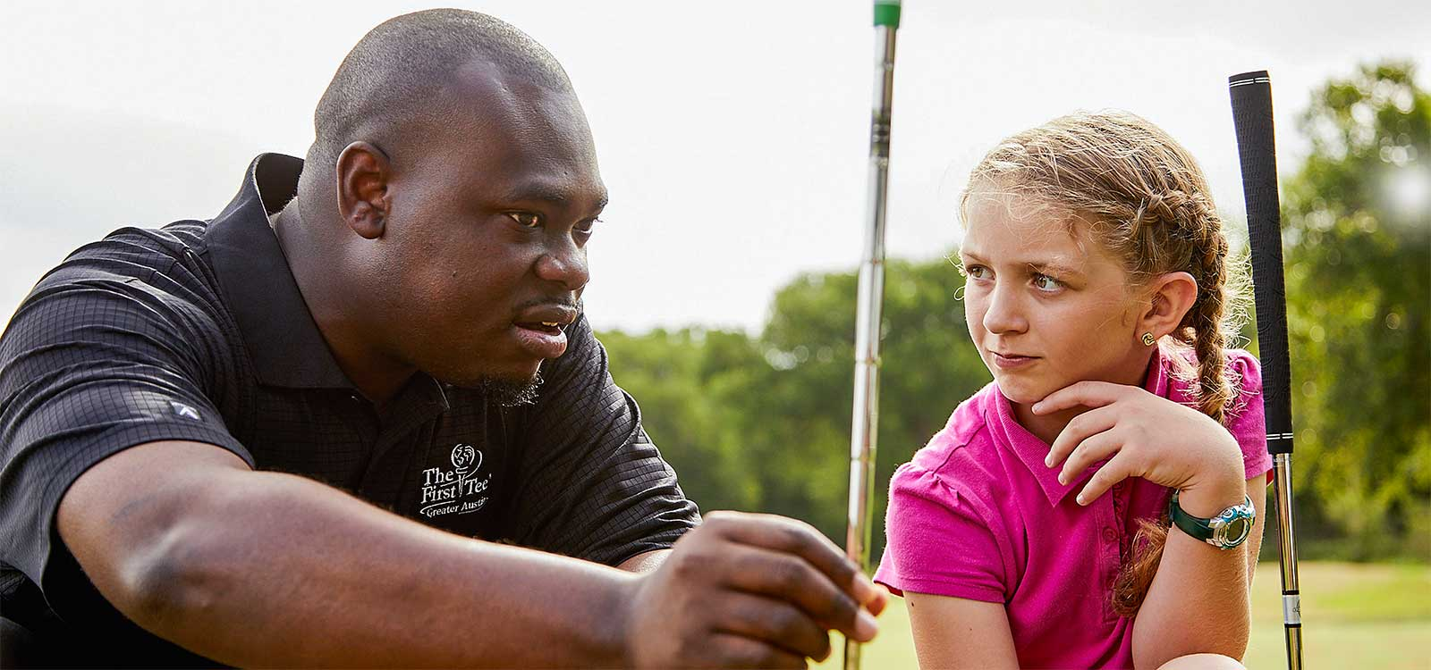 Jordan Spears, alumnus of The First Tee, shares a bit of golf course wisdom with current member Brooklyn.